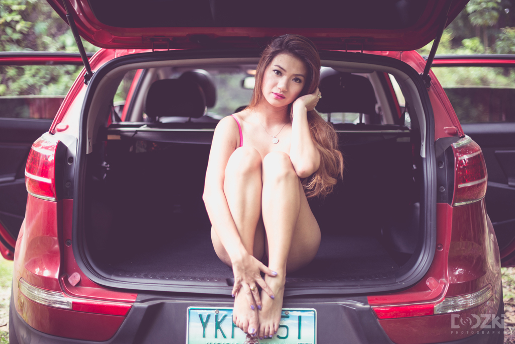 Boudoir session of Marilou sitting at the center of the car
